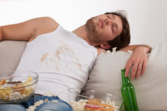 Dirty drunk lounger. A lounger sleeping in a dirty clothes on a couch with snacks and beer Stock Images