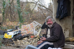 Dirty and drunken. Drunken slovenly homeless man sitting on his property Stock Photography