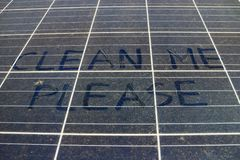 Dirty Dusty Solar Panels with Text Clean Me Please. Dirty Dusty Solar Panels with Hand Writing Text CLEAN ME PLEASE royalty free stock photography