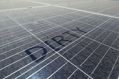 Dirty Dusty Solar Panels with Text DIRTY. The solar panel should be clean regularly to keep it power generating performance royalty free stock images