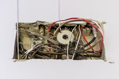 Dirty electric, television and Internet cables and wires in a rectangular recess in the wall of an old residential building stock image