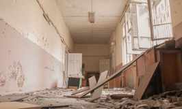 Dirty empty corridor at abandoned school building. Abandoned corridor and destroyed desks and lockers are seen in an old school building Sofia, Bulgaria, May 12 Royalty Free Stock Images