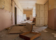 Dirty empty corridor at abandoned school building. Abandoned corridor and destroyed desks and lockers are seen in an old school building Sofia, Bulgaria, May 12 Royalty Free Stock Photos