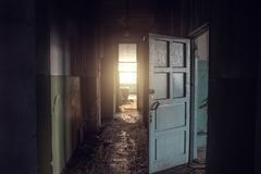 Dirty empty dark corridor in abandoned building, doors, light in the end, perspective, way to freedom stock photo