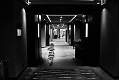 Little girl in dark corridors and light in the building. Black and white. Stock Photos