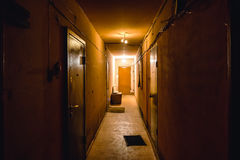Dirty empty dark corridor in apartment building, doors, lighting lamps Royalty Free Stock Photo