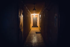 Dirty empty dark corridor in apartment building, doors, lighting lamps. Perspective, in yellow-orange tones, copy space Stock Images