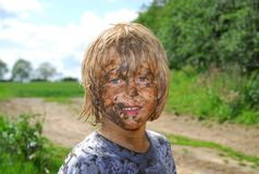 Dirty Face. Young blonde boy smiles through dirty face after outdoor game royalty free stock photography
