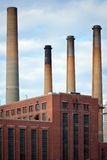 Dirty Factory Smoke Stacks. Over an old brick building Stock Image