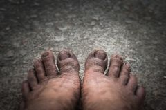 Dirty feet on the Cement floor. This dirty feet. old and ugly on the Cement floor. in the dark tone and dismal mood stock images