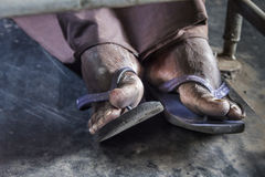 Dirty feet in flip-flops. Workers´ or peasants´ feet in flip-flops in a train in Asia stock photos