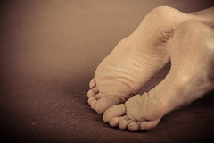 Dirty feet laying on carpet Royalty Free Stock Image