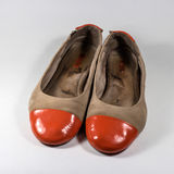 Dirty female shoes with orange socks glossy. Royalty Free Stock Photography