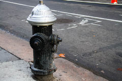 Dirty fire hydrant on the street. Black dirty fire hydrant on the street Stock Image