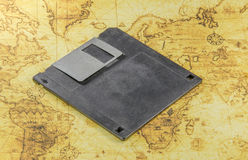 Dirty floppy disk on a old world map Royalty Free Stock Photo