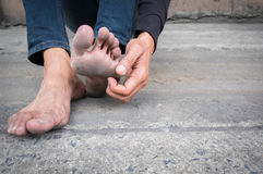 Dirty foot of a man sitting on old concrete floor. Royalty Free Stock Photos