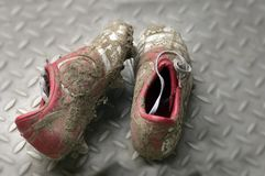 Dirty football or soccer boots. Pair of dirty football or soccer boots on changing room floor Royalty Free Stock Photo