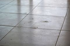 Dirty footprints on white tile stock photo