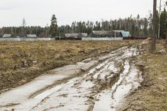 Dirty forest impassable road in the spring thaw broken by melting snow and broken by heavy vehicles. Passing in the forest of the. Moscow region. Russian royalty free stock image
