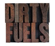 Dirty fuels in letterpress wood type. The phrase 'dirty fuels' in ink-stained wood type isolated on white Stock Images
