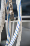 Dirty Garden Hose. A garden hose displays the contrast between the pristine white and blue striped loop of the hose that is clean with the filthy, dirt embedded stock image