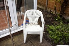 Dirty garden plastic chairs ready for cleaning. Home improvements and renovations. Plastic objects in the garden. Old and used gar. Den furniture. White plastic Stock Images