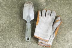 Dirty garden shovel and gloves on concrete floor. Top view Stock Photography