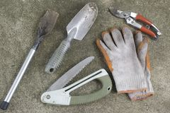 Dirty Gardening tools, shovel, gloves, pruning shears and saw. On concrete floor Royalty Free Stock Photo