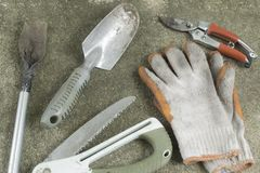 Dirty Gardening tools, shovel, gloves, pruning shears and saw. On concrete floor. Top view Royalty Free Stock Photography