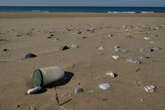 Dirty Glass container sea pollution on sandy beach ecosystem,garbage on sea coast stock photos