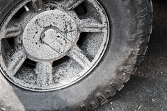 Dirty gray car wheel stands on rural road Royalty Free Stock Photo