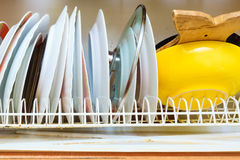 Dirty grubby drainer with clean dishes in kitchen. Royalty Free Stock Photo