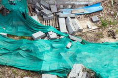Dirty grunge dirty building yard with scattered materials and messy mess, green cloth stock photography