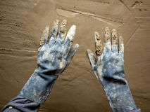 Dirty grunge gloves hands on cement mortar wall Royalty Free Stock Photo