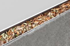 Dirty gutter clogged with oak leaves. royalty free stock photography