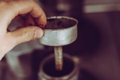 Dirty Hand holding coffee percolator with coffee powder Stock Image
