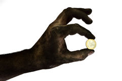 Dirty hand holding one euro coin. Stock Photos