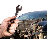 Dirty hand holding wrench and broken car Stock Photo