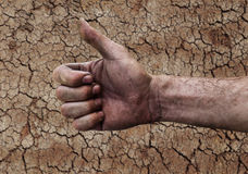 Dirty hand of a man with thumbs up on soil stock image