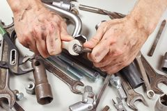Dirty hand of repairman with wrench to tighten the nut. Dirty hand of repairman with a wrench to tighten the nut Royalty Free Stock Images