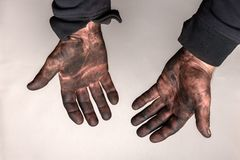 Dirty hands in car masut black oil on gray background. stock photos