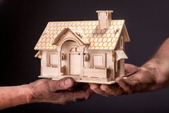 Dirty hands of the country's farmers, holding a model house,buyi. Human hands holdilg small model of house Royalty Free Stock Photo