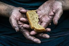 Dirty hands homeless poor man with piece of bread in modern capitalism society. Dirty hands homeless poor man with piece of bread royalty free stock image