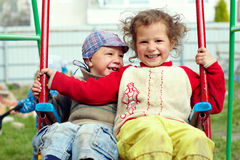 Dirty but happy little gypsy siblings on swings Stock Photo