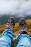Dirty hiking shoes with mountains and clouds in the background. Dirty hiking shoes and legs wearing blue jeans with mountains and clouds in the background Stock Photography