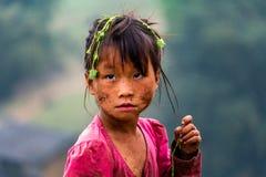Dirty Hmong ethnic minority child portrait Ha Giang Vietnam. Ha Giang, Vietnam - March 16, 2018: Portrait of a wild Hmong ethnic minority girl with grass in her stock photo
