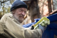 Dirty homeless man holding packing for eggs, standing by the trash can. Royalty Free Stock Photos