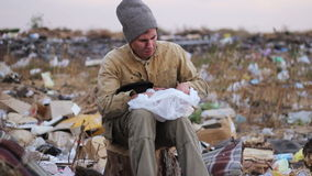 Dirty homeless man sits on a stump in the trash. And eat stock footage
