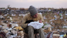 Dirty homeless man sits on a stump in the trash. And eat the food from the  bag stock video footage