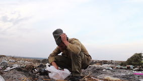 Dirty homeless man sits on the trash and eat bread stock footage
